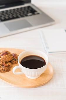 Café noir et biscuits avec ordinateur portable et carnet de notes