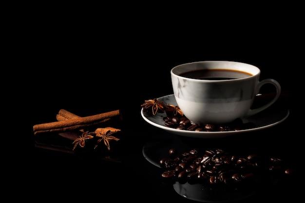 Café noir chaud dans une pâte de tasse de marbre blanc réfléchi sur un plancher de verre noir