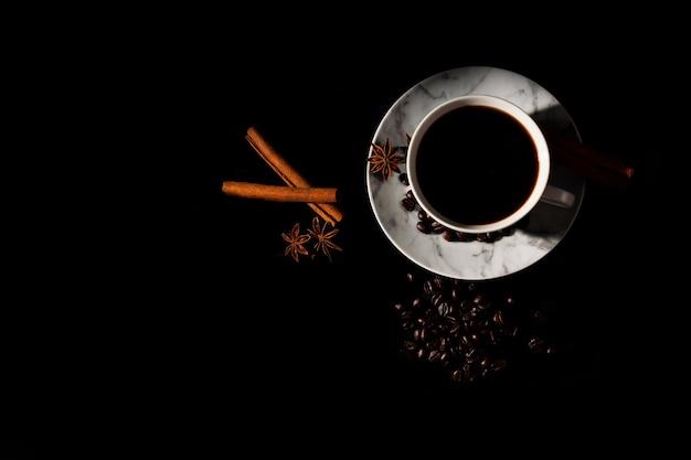 Café noir chaud dans une tasse en marbre blanc avec une pâte anisée étoilée réfléchie
