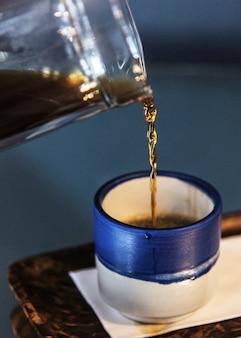 Café noir dans une petite tasse bleue
