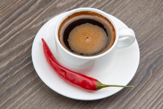 Café noir dans une tasse blanche avec du piment rouge sur une assiette.