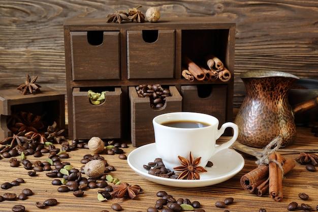 Café noir dans une tasse blanche et épices sur une table en bois