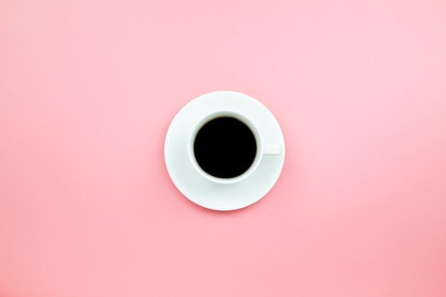 Café noir dans une tasse blanche sur fond rose style pastel
