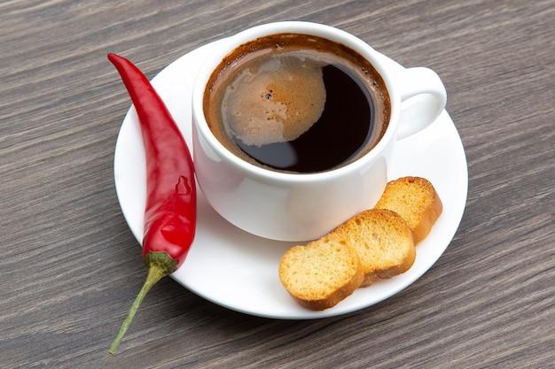 Café noir dans une tasse blanche avec piment rouge et craquelins sur assiette, vue du dessus