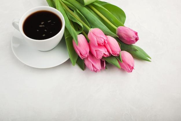 Café noir dans une tasse blanche et des tulipes.