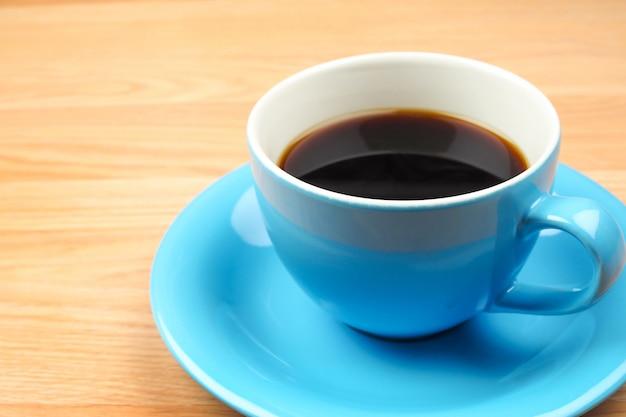 Café noir dans une tasse bleue sur fond de table en bois marron