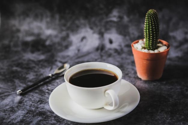 Café noir dans une tasse à café blanche et cactus placé