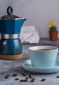 Café noir dans une tasse, cafetière geyser et grains de café sur une planche