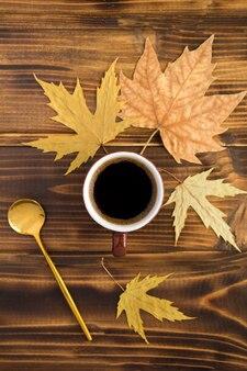 Café noir dans la tasse en céramique brune et feuilles jaunes sur le fond en bois. vue de dessus. composition d'automne. emplacement vertical.