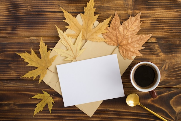 Café noir dans la tasse en céramique, papier blanc pour le texte et feuilles sèches sur le fond en bois marron. vue de dessus. espace de copie. composition d'automne.