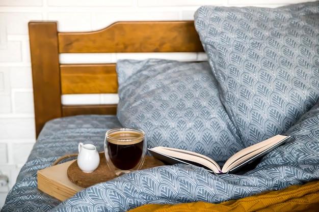 Café noir dans une tasse transparente au lit le matin d'automne