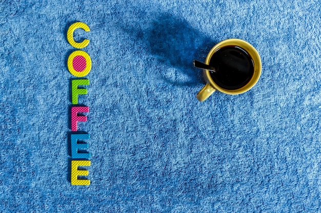 Café noir dans un verre avec un fond de tissu bleu et un matériau en liège qui lit le café