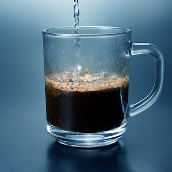 Le café noir est versé dans une tasse transparente. boisson chaude