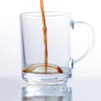 Le café noir est versé dans une tasse transparente sur fond blanc. boissons chaudes