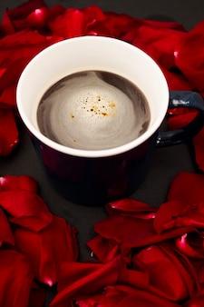Café noir sur fond noir avec pétales de rose