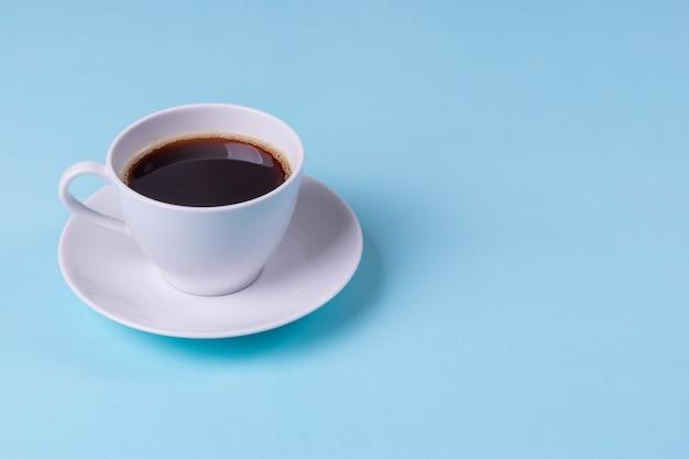 Café noir sur fond de table bleu pâle