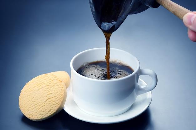 Café noir fraîchement moulu des turcs versé dans une tasse blanche. boisson chaude