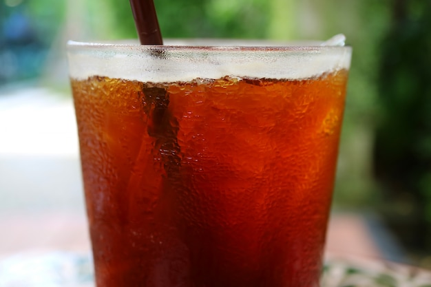 Café noir glacé fermé en verre transparent avec condensation, arrière-plan flou