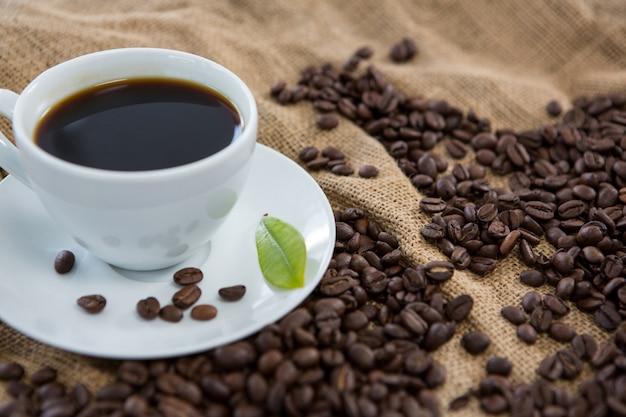 Café noir, grains de café et feuille sur sac