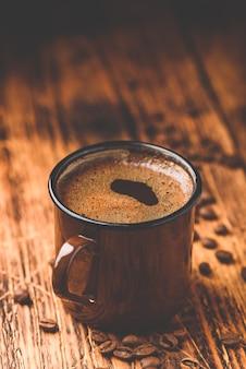 Café noir infusé dans une tasse en métal sur une surface en bois