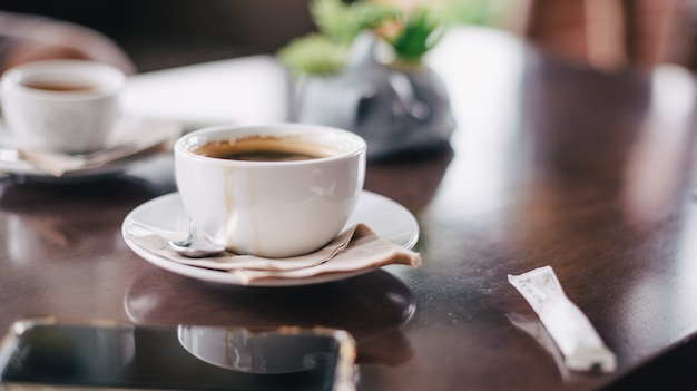 Café noir le matin placé sur une table en bois et un téléphone.