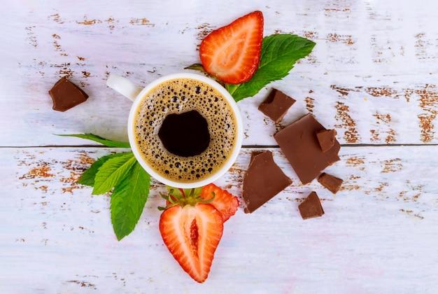 Café noir naturel avec fraise et chocolat sur table en bois blanc