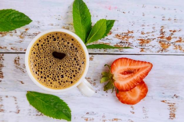 Café noir naturel avec fraise sur table en bois blanc. vue de dessus.