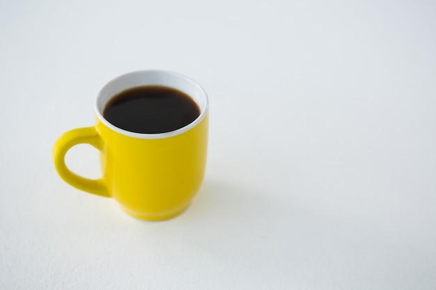 Café noir servi dans une tasse jaune