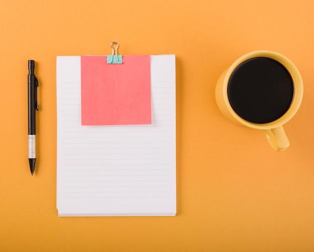 Café noir; stylo et papier blanc avec une note adhésive sur fond orange