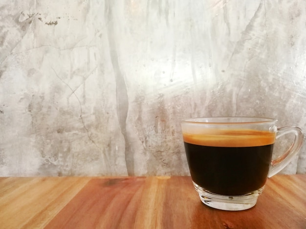 Café noir sur la table en bois avec fond grunge gris et espace coppy.