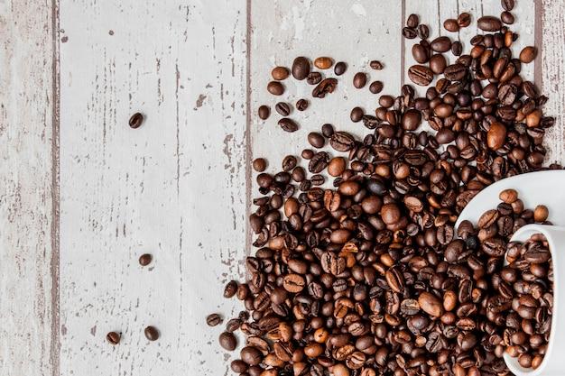 Café noir en tasse blanche et grains de café sur fond en bois clair.