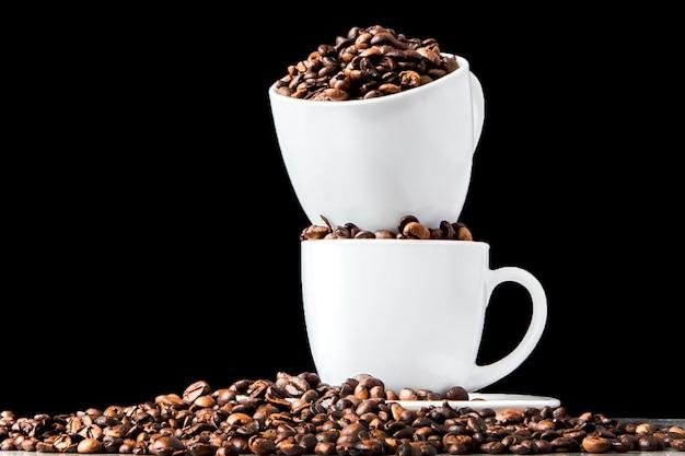 Café noir en tasse blanche et grains de café sur fond noir