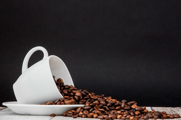 Café noir en tasse blanche et grains de café. fond