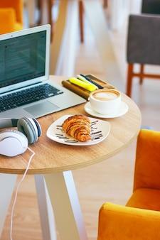 Café, ordinateur portable et croissants pour montrer un petit déjeuner d'affaires sur la table du bureau le matin.