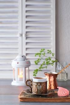 Café oriental cuit dans une cafetière turque traditionnelle en cuivre et servi dans une tasse assortie