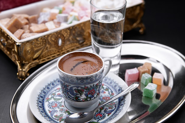 Café oriental, avec de l'eau, loukoums, sur une plaque de métal, sur fond sombre