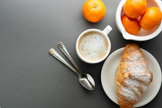 Café de petit déjeuner avec croissant, agrumes français, pâtisserie, tasse de café ou café au lait. la caféine est une drogue.