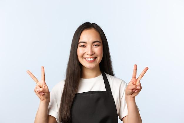Café, petite entreprise et concept de démarrage. gros plan d'une femme asiatique joyeuse, barista, employée de magasin ou de café en masque médical, souriante optimiste et montrant des signes de paix en v, fond blanc