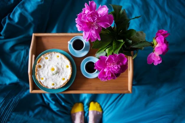 Café, pivoines roses, cheesecake sur un plateau en bois, vue de dessus.