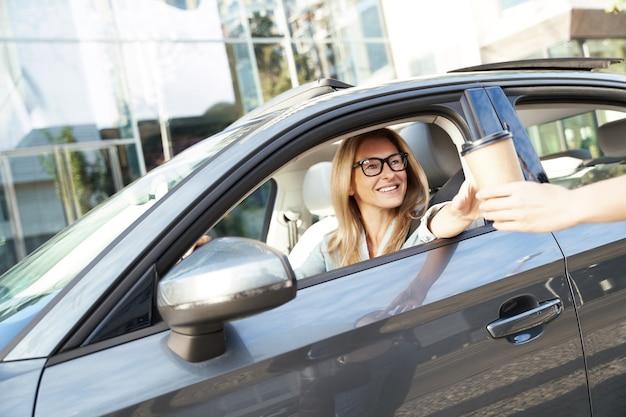 Café pour aller heureuse femme d'affaires caucasienne assise derrière le volant de sa voiture moderne et
