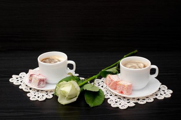 Café pour deux avec des bonbons orientaux, une rose blanche sur un fond noir