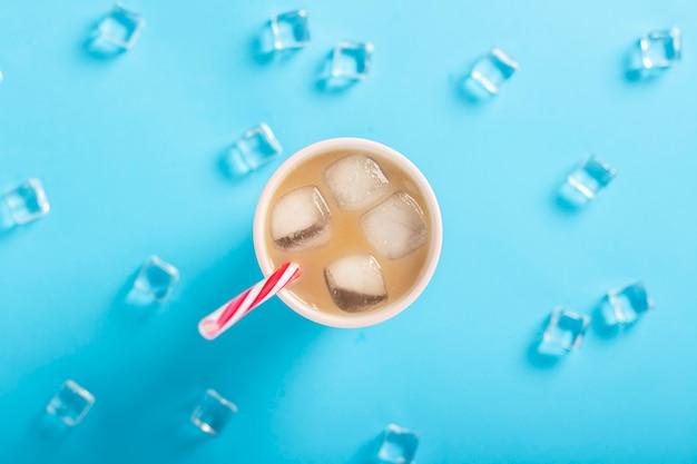 Café rafraîchissant avec du lait et de la glace dans un verre, des glaçons sur fond bleu. concept d'été, glace, cocktail rafraîchissant, soif. mise à plat, vue de dessus