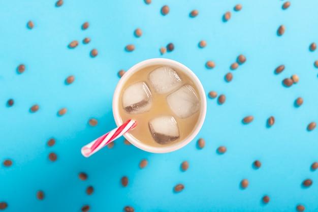 Café rafraîchissant avec du lait et de la glace dans un verre et des grains de café sur un fond bleu. concept d'été, glace, cocktail rafraîchissant, soif. mise à plat, vue de dessus