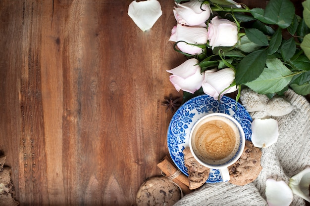 Café romatique dans une tasse sur un fond en bois avec un plaid, un bouquet de roses blanches et un confort d'automne. bonjour. vue supérieure. copier l'espace