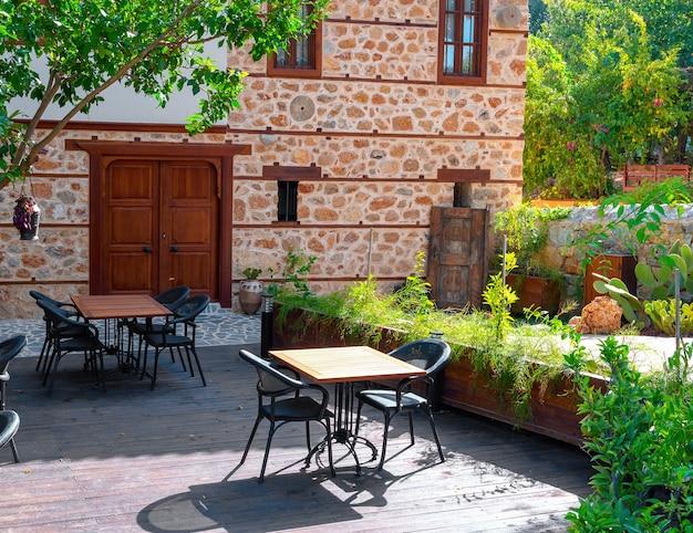 Café de la rue éclairé par le soleil avec des tables vides à alanya, turquie