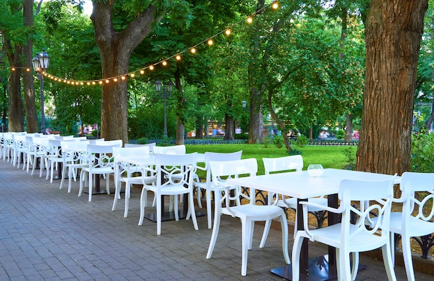 Café de rue en plein air en plein air - chaises et tables blanches, décorer