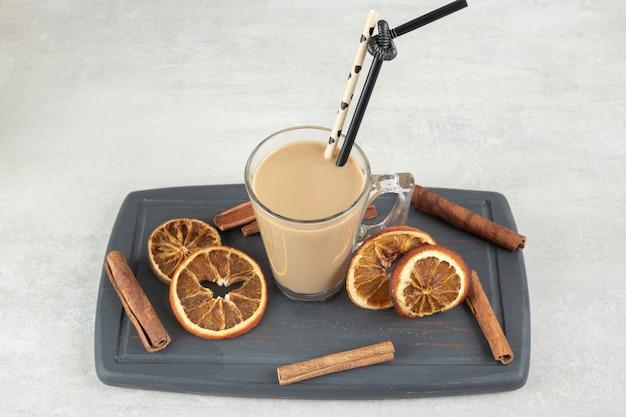 Café savoureux, bâtons de cannelle et tranches d'orange sur plaque sombre