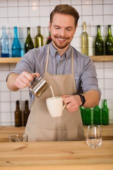 Café savoureux. enthousiaste bel homme agréable debout au comptoir et préparant un verre tout en travaillant comme barista professionnel