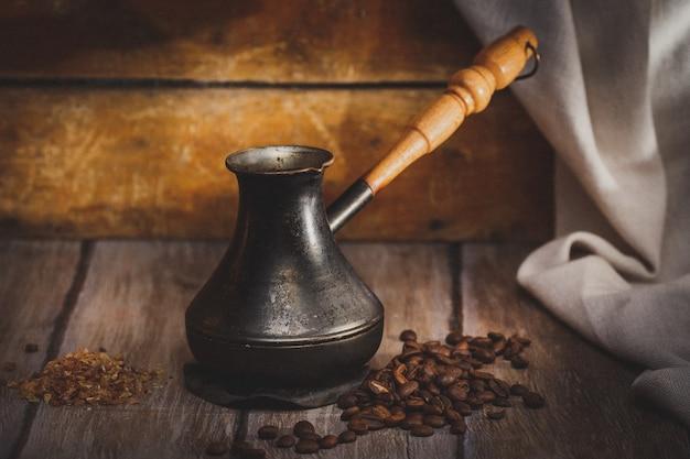 Café soudé en cezve sur une surface en bois, style rustique