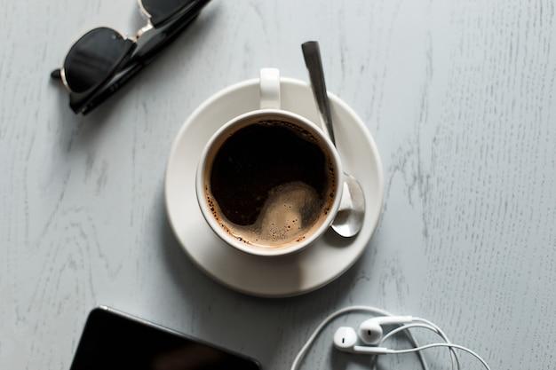 Café sur la table en bois avec le téléphone avec des écouteurs et des lunettes de soleil